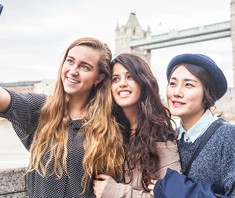 Multiracial group of girls taking a selfie in London with Tower Bridge on background. The group consists of three girls, one is from Korea, one from Spain and one from Holland
